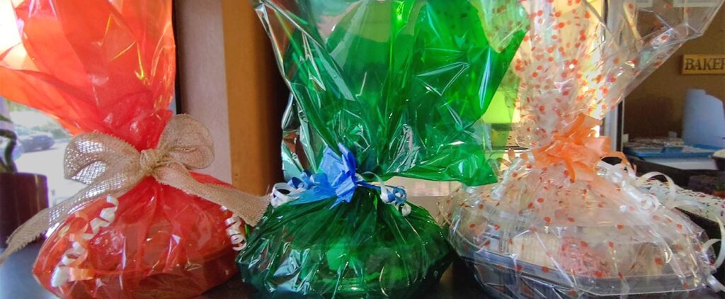 Three gift baskets, festively decorated and fillded with baked goods
